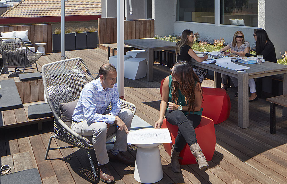 Senior Associate, Greg McClure, AIA, LEED AP, meeting with a team member on our outdoor deck.